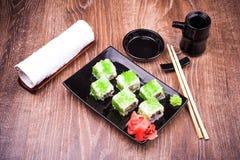 El rollo de sushi fijó en caviar verde con el jengibre, la salsa de soja, la toalla y los palillos Foto de archivo