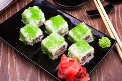 El rollo de sushi fijó en caviar verde con el jengibre y los palillos Foto de archivo libre de regalías