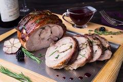 El rollo del muslo de Turquía rellenó Rosemary, el tomillo, el perejil, la mantequilla y el tocino en el top con la salsa picante Foto de archivo libre de regalías