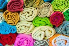 El rollo formó la seda, las bufandas de la cabeza de la cachemira o los mantones coloridos tradicionales apilados fotografía de archivo libre de regalías
