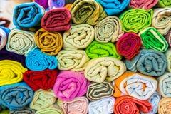 El rollo formó la seda, las bufandas de la cabeza de la cachemira o los mantones coloridos tradicionales apilados imagenes de archivo