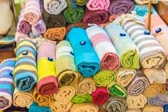 El rollo formó la seda, las bufandas de la cabeza de la cachemira o los mantones coloridos tradicionales apilados imagen de archivo libre de regalías