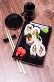 El rollo picante del sishi fijó con el jengibre, la salsa de soja, la toalla y los palillos Imágenes de archivo libres de regalías
