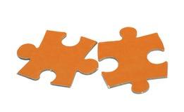 El rompecabezas anaranjado está en un fondo blanco Fotografía de archivo libre de regalías