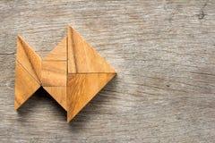 El rompecabezas chino del rompecabezas chino en pescados forma en fondo de madera Fotos de archivo