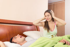 El roncar joven y la esposa del hombre no pueden dormir Foto de archivo libre de regalías