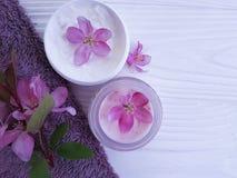 El rosa cosmético poner crema del balneario de la relajación florece orgánico en la toalla de madera blanca Foto de archivo