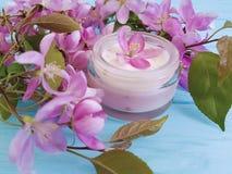 El rosa cosmético poner crema del ingrediente de la loción florece en de madera azul Fotografía de archivo