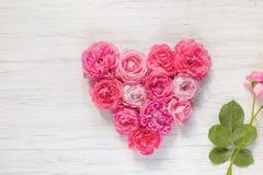 El rosa del vintage subió las flores en la forma de un corazón y de una rama en un fondo de madera imagen de archivo