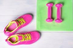 El rosa fijó para el deporte de zapatillas de deporte y del concepto de las pesas de gimnasia en piso gris Fotos de archivo