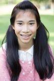 El rosa hermoso adolescente del vestido de la muchacha feliz y se relaja en parque Imagen de archivo