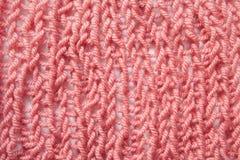 El rosa o el rojo que hacía punto texturizó el fondo de las lanas, cierre para arriba, estilo del vintage Foto de archivo libre de regalías