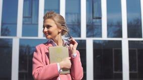 El rosa que lleva de la mujer se cierra con la tableta al aire libre almacen de video