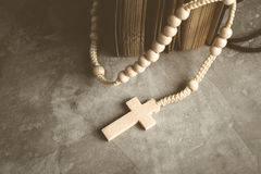El rosario católico gotea con el libro viejo en rezo de la tabla del cemento, Rosa Imágenes de archivo libres de regalías