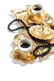 El rosario de oro de las tazas de café gotea el fondo blanco el Ramadán Foto de archivo libre de regalías