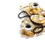 El rosario de oro de las tazas de café gotea el fondo blanco el Ramadán Imagen de archivo