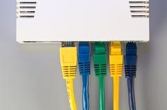 El router de la oficina conectó con cinco cordones de remiendo multicolores con los conectores RJ45 Fotografía de archivo libre de regalías