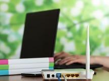 El router está conectado con la red, el ordenador portátil y las carpetas con los documentos en la tabla Fotografía de archivo libre de regalías