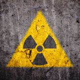 El símbolo amonestador del peligro atómico radiactivo de la radiación ionizante en forma amarilla triangular pintó el muro de cem foto de archivo