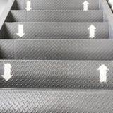 El símbolo de la manera hacia arriba y hacia abajo en las escaleras Las flechas fueron pintadas en blanco en la escalera de acero fotos de archivo