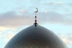 El símbolo del Islam es una luna creciente de oro encima de la mezquita Alminar en la tarde azul del cielo de la mañana con las n imagen de archivo libre de regalías