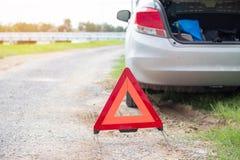 El símbolo rojo del triángulo está situado en el camino para advertir que el coche se rompió fotos de archivo libres de regalías