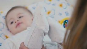 El ` s de la madre da a movimientos las pequeñas piernas del ` s del bebé metrajes