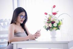 El ` s de la muchacha que mira y goza de smartphone en su sittin de la mano y de la risa Imagenes de archivo