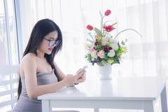 El ` s de la muchacha que mira y goza de smartphone en su sittin de la mano y de la risa Fotos de archivo libres de regalías