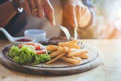 El ` s de la mujer de Asia da la consumición del filete de la carne con la diversión y feliz Imagen de archivo libre de regalías