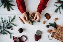 El ` s de la mujer da la fabricación de un regalo de Navidad en la tabla de madera blanca Imagen de archivo libre de regalías