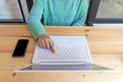 El ` s de la mujer da mecanografiar en un ordenador portátil con el teléfono elegante en la tabla de madera Fotos de archivo