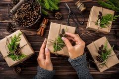 El ` s de la mujer da paquetes y adorna los regalos de la Navidad o del Año Nuevo Fotos de archivo