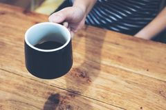 El ` s de la mujer da sostener un café sólo en la tabla de madera del vintage Foto de archivo