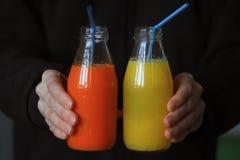 El ` s de la mujer da sostener una botella de verduras frescas y de zumo de fruta, fondo oscuro Fotografía de archivo libre de regalías