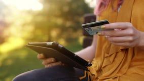 El ` s de la mujer del primer da sostener una tarjeta de crédito y usar la PC de la tableta, compras en línea, al aire libre almacen de metraje de vídeo