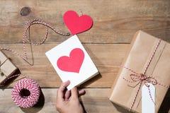 El ` s de la tarjeta del día de San Valentín adornó la caja de regalo sobre fondo de madera Visión desde Foto de archivo