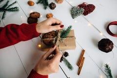 El ` s de las mujeres da la fabricación de un regalo de la Navidad Imágenes de archivo libres de regalías