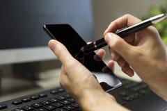 El ` s de las mujeres da la pantalla del teléfono de los tactos con la pluma para la pantalla táctil foto de archivo libre de regalías