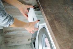 El ` s de las mujeres da sostener un envase de detergente fotografía de archivo