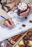 El ` s de las mujeres da sostener una pluma y una taza de cacao o de chocolate caliente Fotos de archivo