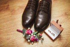 El ` s de los hombres calza boutonniere y los anillos de bodas en una caja, contra la perspectiva de un piso de madera Detalles d Foto de archivo