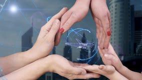 El ` s de los hombres, el ` s de las mujeres y las manos del ` s de los niños muestran un avión del holograma 3d almacen de metraje de vídeo