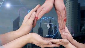 El ` s de los hombres, el ` s de las mujeres y las manos del ` s de los niños muestran un helicóptero del holograma 3D almacen de video