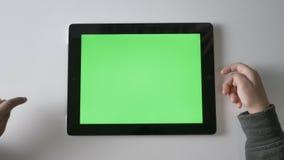 El ` s de los niños da birlar en una tableta, pantalla verde, concepto del chromakey, fps superiores del tiro 60 almacen de metraje de vídeo