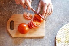 El ` s del adolescente da los tomates del corte con el cuchillo en tabla de cortar de madera Imágenes de archivo libres de regalías