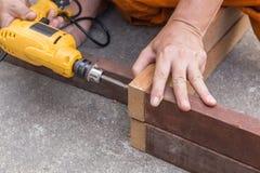 El ` s del carpintero da la madera de la perforación del trabajador del hombre Foto de archivo libre de regalías