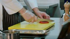 El ` s del cocinero da cortar el paprika rojo curado y ponerlo así como otros ingredientes metrajes