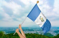 El ` s del hombre joven da orgulloso agitar la Guatemala bandera nacional en el cielo, representación de la parte 3D Imágenes de archivo libres de regalías