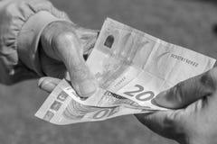 El ` s del hombre mayor da sostener el billete de banco euro Pensionistas luchadores Fotos de archivo libres de regalías